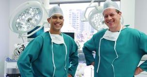 Ritratto dei chirurghi maschii che stanno con le mani sulla stanza in funzione delle anche video d archivio