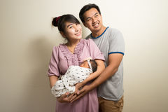 Ritratto dei genitori asiatici e di sei mesi della neonata a casa Fotografia Stock