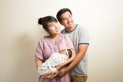 Ritratto dei genitori asiatici e di sei mesi della neonata a casa Immagine Stock