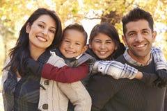 Ritratto dei genitori felici che trasportano sulle spalle i bambini all'aperto Fotografia Stock