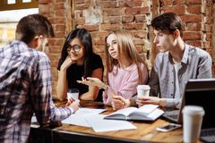 Ritratto dei giovani che si siedono intorno in caffè con un computer portatile Fotografie Stock