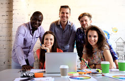 Ritratto dei giovani felici in una riunione che esamina macchina fotografica e sorridere Giovani progettisti che lavorano insieme fotografie stock libere da diritti