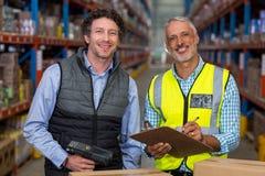 Ritratto dei lavoratori del magazzino che stanno con la lavagna per appunti ed il lettore di codici a barre Fotografie Stock Libere da Diritti