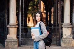 Ritratto dei libri felici e di esame di una tenuta della studentessa della macchina fotografica all'aperto vicino all'università Fotografia Stock