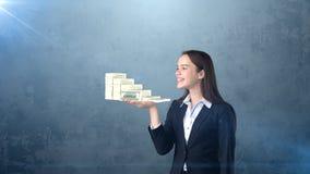 Ritratto dei pacchetti della tenuta della donna del dollaro dei soldi sulla palma aperta della mano, sopra il fondo isolato dello Fotografie Stock