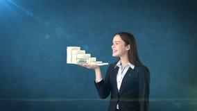 Ritratto dei pacchetti della tenuta della donna del dollaro dei soldi sulla palma aperta della mano, sopra il fondo isolato dello Immagini Stock