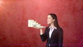 Ritratto dei pacchetti della tenuta della donna del dollaro dei soldi sulla palma aperta della mano, sopra il fondo isolato dello Fotografia Stock