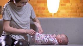 Ritratto dei pannolini cambianti della madre a sua figlia neonata sveglia che si trova sul sofà nel salone archivi video