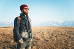 Ritratto dei pantaloni a vita bassa alla moda premurosi con una barba in occhiali da sole ed in un cappello con uno zaino sui pre Fotografia Stock Libera da Diritti