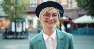Ritratto dei pantaloni a vita bassa allegri in vetri e nella condizione sorridente del cappello all'aperto da solo archivi video
