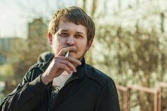 Ritratto dei pantaloni a vita bassa attraenti con la barba, fumante una sigaretta all'aperto Immagini Stock