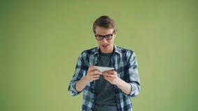 Ritratto dei pantaloni a vita bassa che gioca gioco sullo schermo di contatto dell'aggeggio della tenuta dello smartphone stock footage