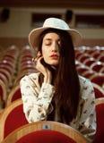 Ritratto dei pantaloni a vita bassa graziosi della ragazza in un cappello d'uso del cinema, sognante da solo Fotografie Stock Libere da Diritti