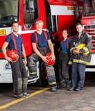 Ritratto dei pompieri sorridenti che si appoggiano i camion immagine stock libera da diritti