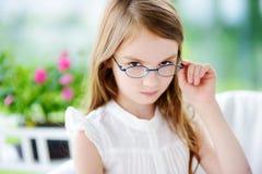 Ritratto dei vetri d'uso della bambina sveglia a casa Visione, salute, concetto di oftalmologia immagini stock libere da diritti