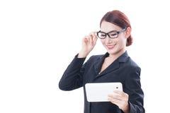 Ritratto dei vetri d'uso della giovane donna di affari facendo uso della compressa fotografie stock