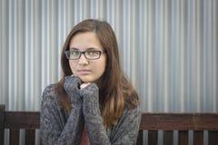 Ritratto dei vetri d'uso della ragazza teenager malinconica del topo di biblioteca Fotografia Stock