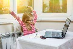 Ritratto dei vetri d'uso di una ragazza di 7 anni sveglia, facendo uso di un lapt Fotografia Stock