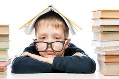 Ritratto dei vetri d'uso di uno scolaro stanco con un libro sul suo Immagini Stock Libere da Diritti