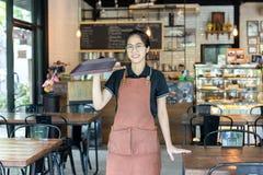Ritratto dei waiteress che tengono vassoio vuoto in una caffetteria fotografie stock