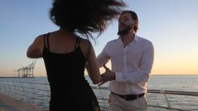 Ritratto del bachata latino ballante delle giovani coppie attraenti vicino al mare o all'oceano Fondo di luce solare Ora legale,  video d archivio