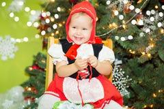 Ritratto del bambino della ragazza in vestito un cappello rosso per il Natale intorno ad un abete decorato Bambino sul nuovo anno Immagine Stock Libera da Diritti