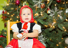 Ritratto del bambino della ragazza in vestito un cappello rosso per il Natale intorno ad un abete decorato Bambino sul nuovo anno Fotografia Stock