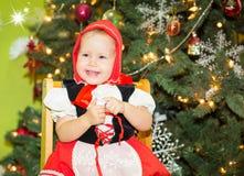 Ritratto del bambino della ragazza in vestito un cappello rosso per il Natale intorno ad un abete decorato Bambino sul nuovo anno Immagine Stock