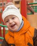 Ritratto del bambino di risata in un cappuccio ed in un rivestimento Fotografia Stock Libera da Diritti