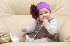 Ritratto del bambino sulla presidenza che rosicchia un merletto Fotografia Stock