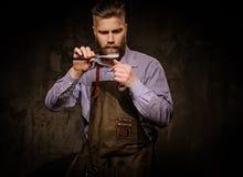 Ritratto del barbiere alla moda con la barba e degli strumenti professionali su un fondo scuro fotografia stock