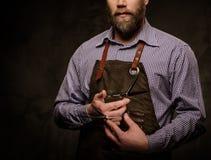 Ritratto del barbiere alla moda con la barba e gli strumenti professionali isolati su un fondo scuro immagine stock