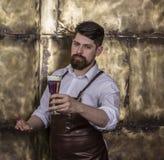 Ritratto del barista brutale che sta e che sorride nella barra immagini stock