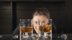 Ritratto del barista femminile sorridente felice che esamina macchina fotografica attraverso i vetri del whiskey che stanno dietr stock footage