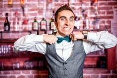 Ritratto del barista o del barista arrabbiato e sollecitato con la cravatta a farfalla Immagine Stock