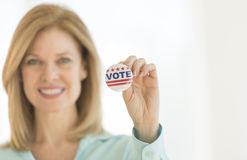 Ritratto del bottone maturo di voto della tenuta della donna Fotografie Stock Libere da Diritti