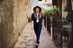 Ritratto del cappello d'uso della giovane bella donna che cammina nella vecchia città Concetto di modo della via modificato immagine stock