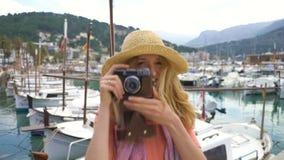 Ritratto del cappello di paglia d'uso della giovane donna che sorride ai precedenti del litorale della macchina fotografica archivi video