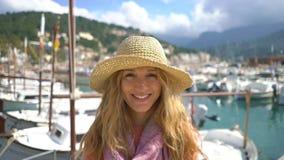 Ritratto del cappello di paglia d'uso della giovane donna che sorride alla macchina fotografica con il fondo del litorale stock footage