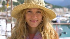 Ritratto del cappello di paglia d'uso della giovane donna che sorride alla macchina fotografica con il fondo del litorale video d archivio
