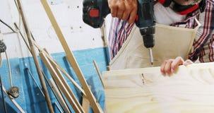 Ritratto del carpentiere concentrato che inchioda una plancia di legno video d archivio