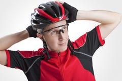 Ritratto del ciclista caucasico maschio che posa in casco protettivo e vetri della strada rossa Fotografie Stock