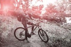 Ritratto del ciclista in mountain-bike maschio con la bicicletta alla foresta Fotografie Stock