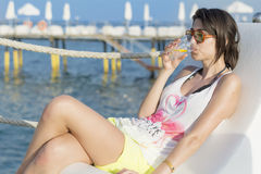 Ritratto del cocktail bevente della giovane donna sulla spiaggia Fotografie Stock Libere da Diritti