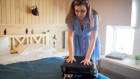 Ritratto del coperchio puching della giovane donna della valigia che prova a chiuderlo immagine stock libera da diritti