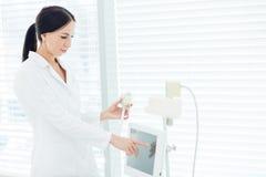Ritratto del cosmetologo sorridente nel unoform medico bianco con l'apparecchiatura di GPL immagine stock libera da diritti