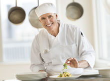 Ritratto del cuoco unico felice Garnishing Pasta Dish Fotografie Stock Libere da Diritti