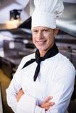 Ritratto del cuoco unico maschio felice che sta con le armi attraversate Immagine Stock