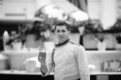 Ritratto del cuoco unico nel bianco al buffet del ristorante con rosso con la mela gialla, buongustaio, toni in bianco e nero di  fotografie stock libere da diritti
