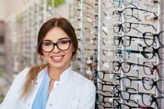 Ritratto del deposito di Woman At Eyeglasses dell'ottico fotografie stock